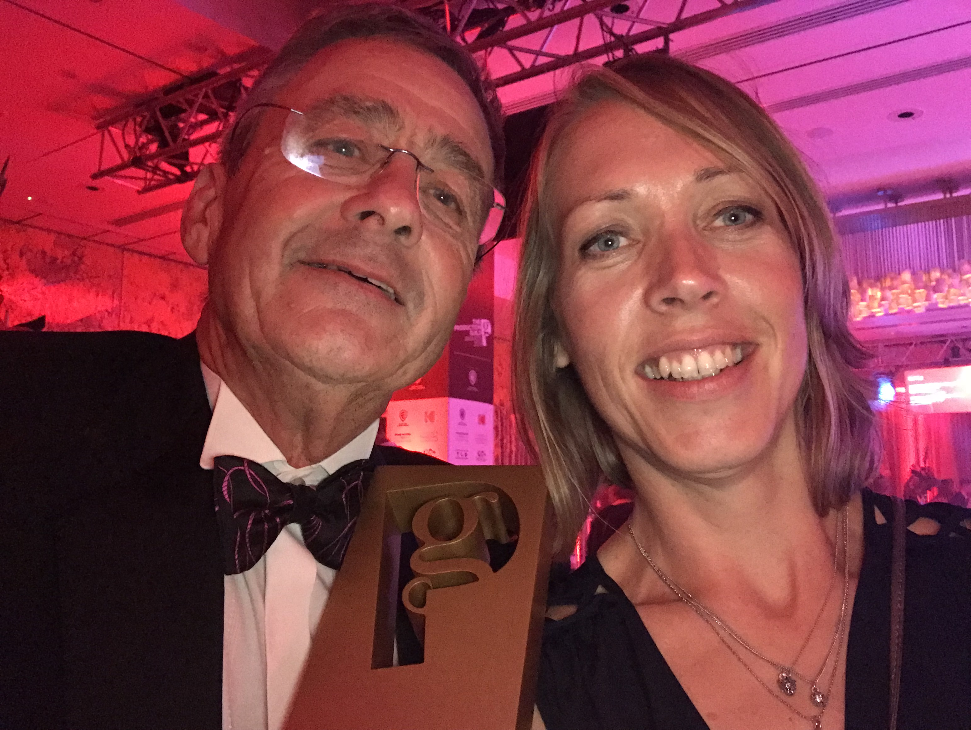 A close up of Gareth holding his award and smiling, with Chloe Chesterton