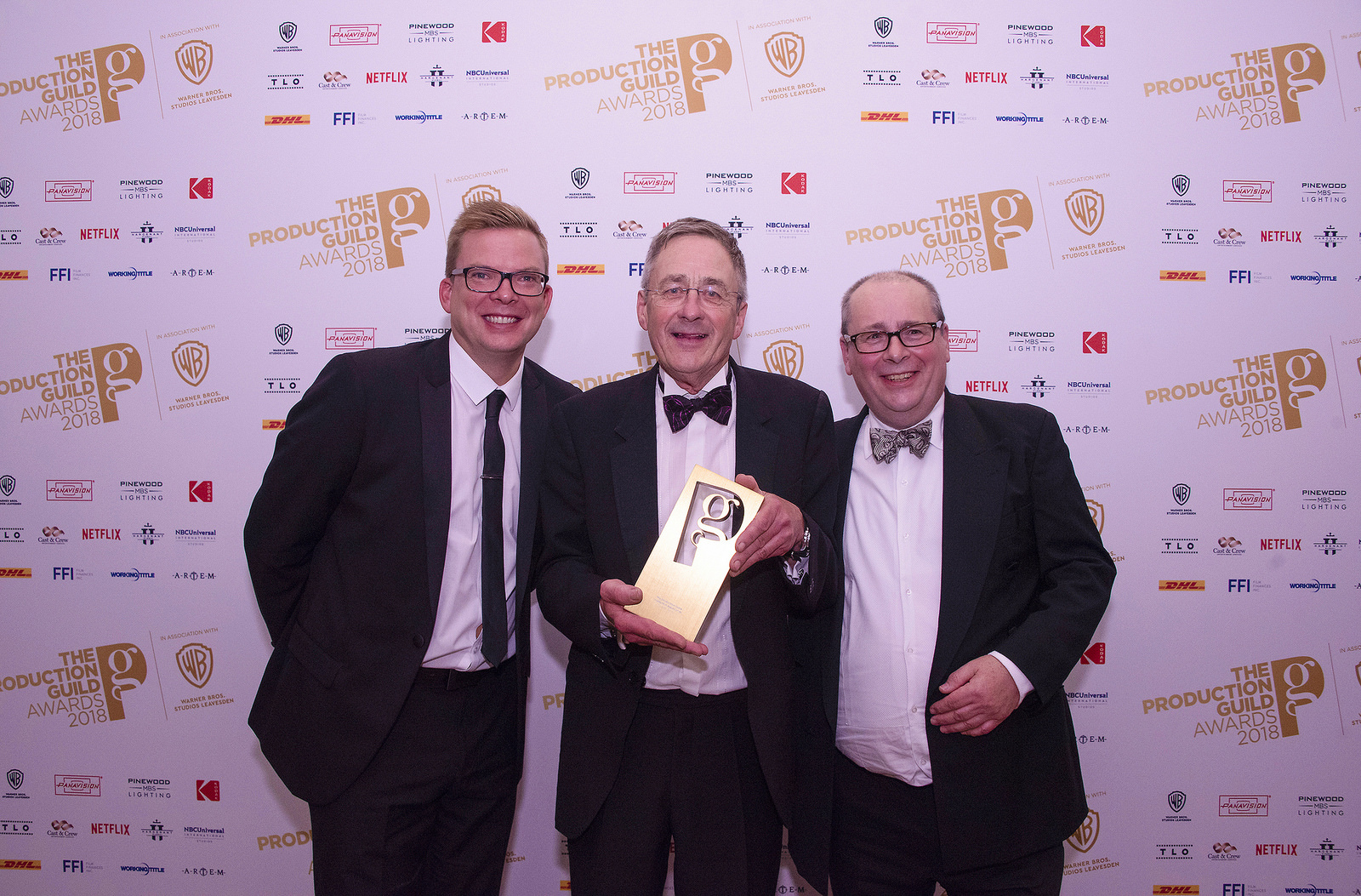 Gareth Tandy standing in a suit with two other men, holding his award